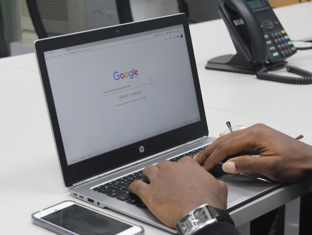 Man searching Google on his laptop