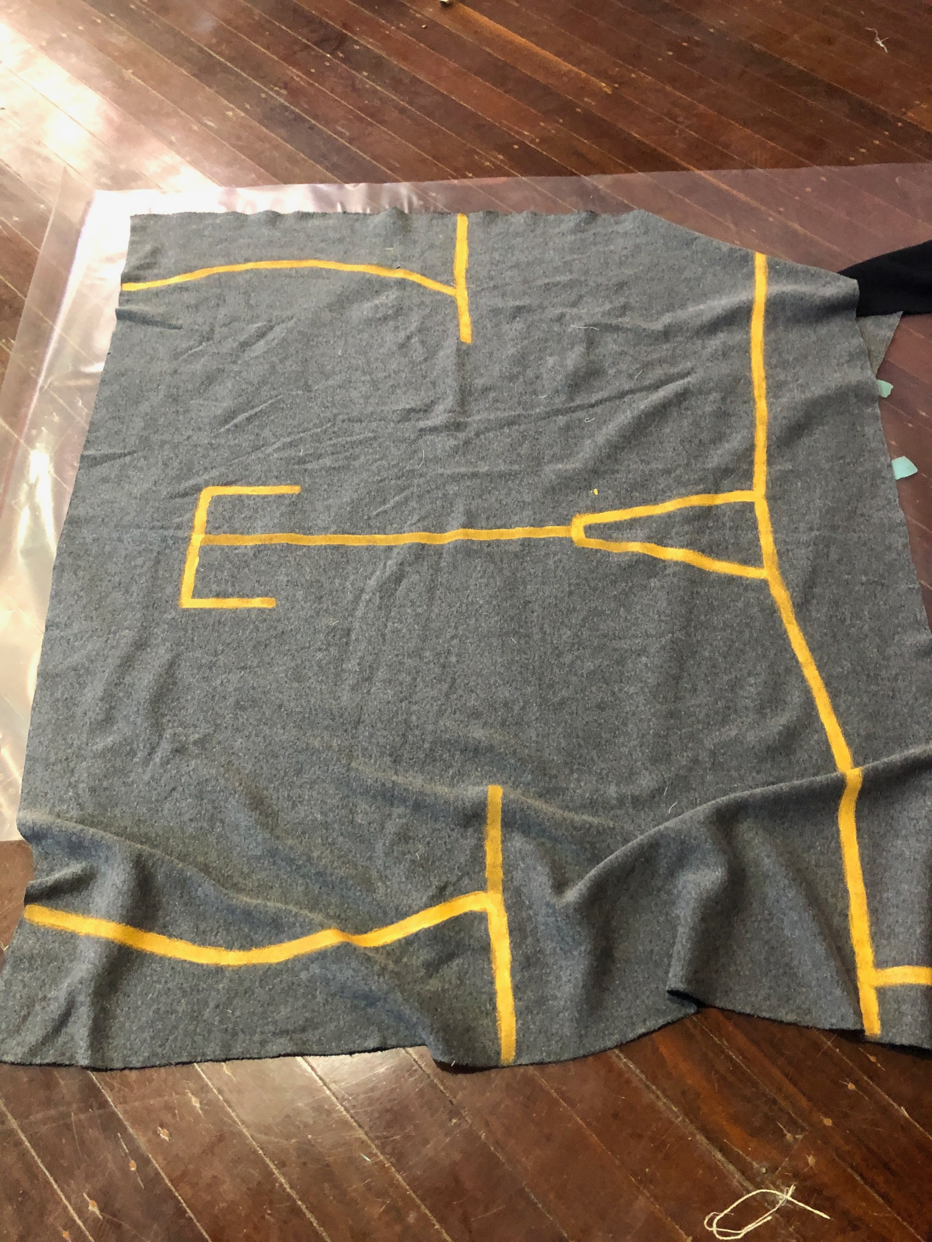 A flat  piece of grey fabric, showing the cutting lines for the bog coat, painted on with house paint.