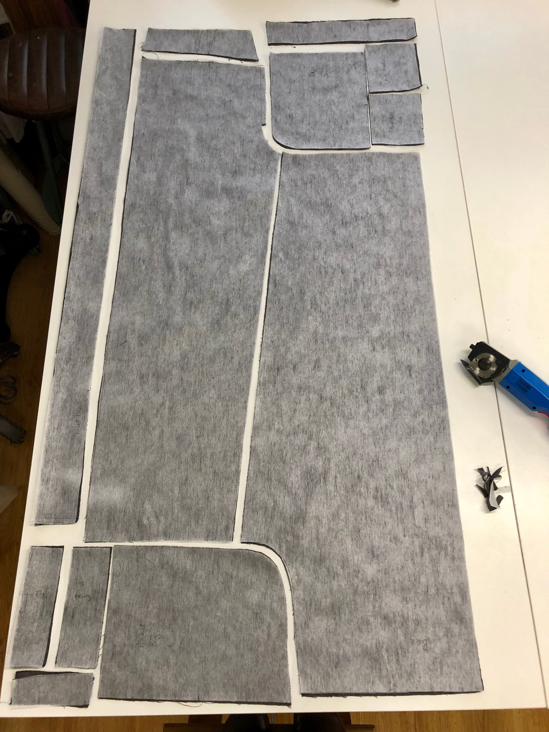 The pieces for a pair of zero waste trousers are shown laid out on a table. A regular pattern has been and modified so the pieces fit on a single rectangle of fabric. Tiny leftover scraps are shown.