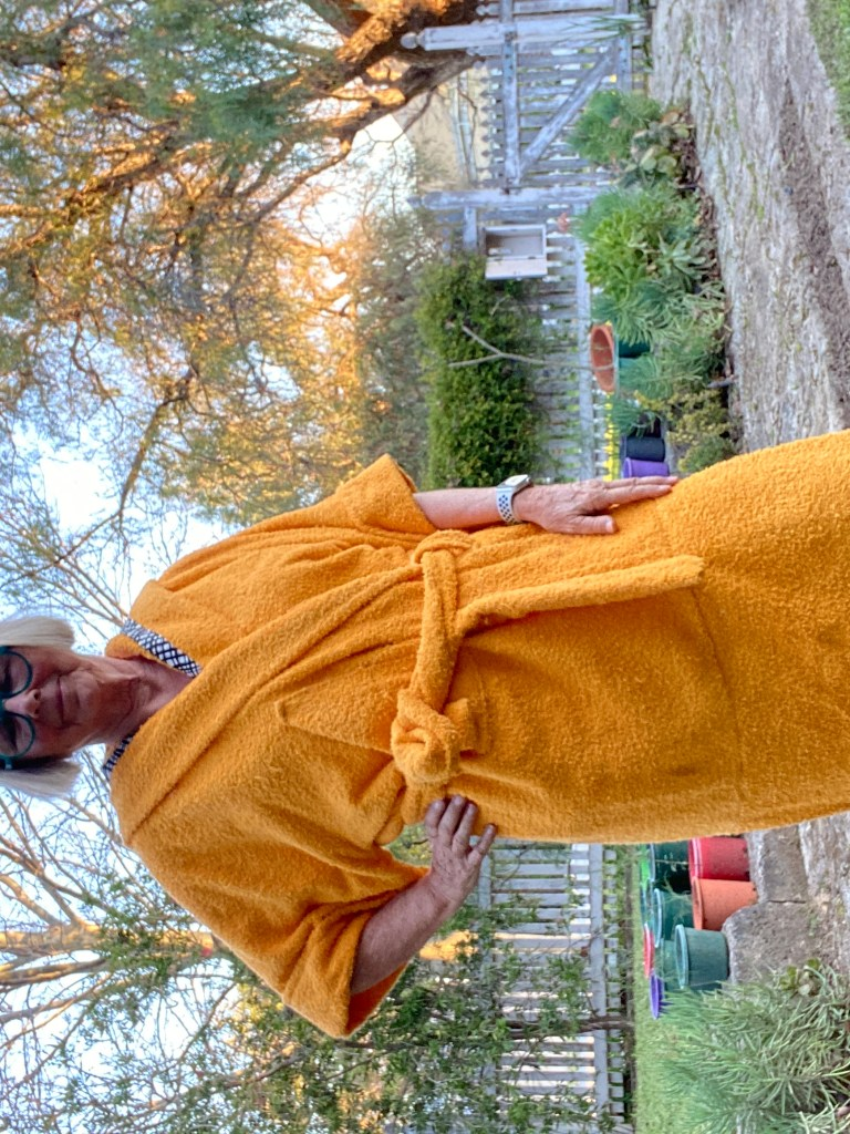 yellow towelling bathrobe showing large piece added to improve length and decency.