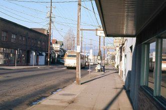 """SE Division @ 35th Place, Portland, OR. For a second I thought """"Open Noon"""" might be a show. A bioswale now occupies the corner where these people wait for the bus. April, 1977"""