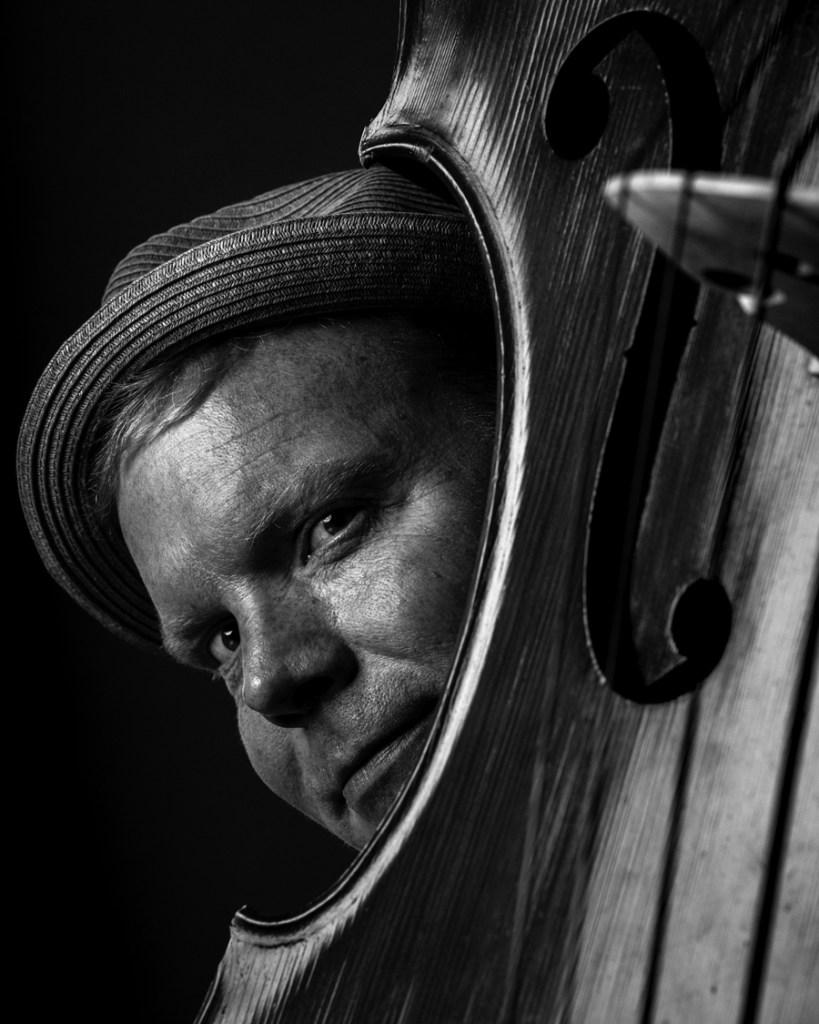 musician peeking from behind a bass