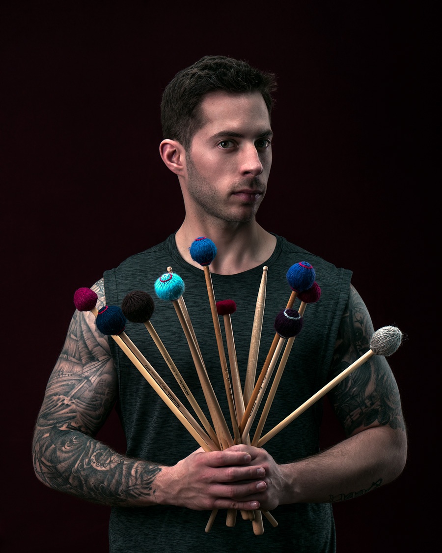 man with drum sticks and drum paddles