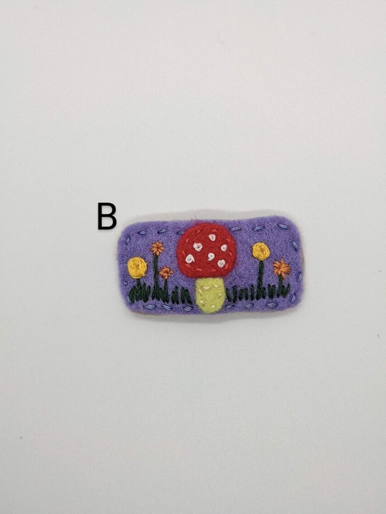 red mushroom on purple background with embroidered flowers