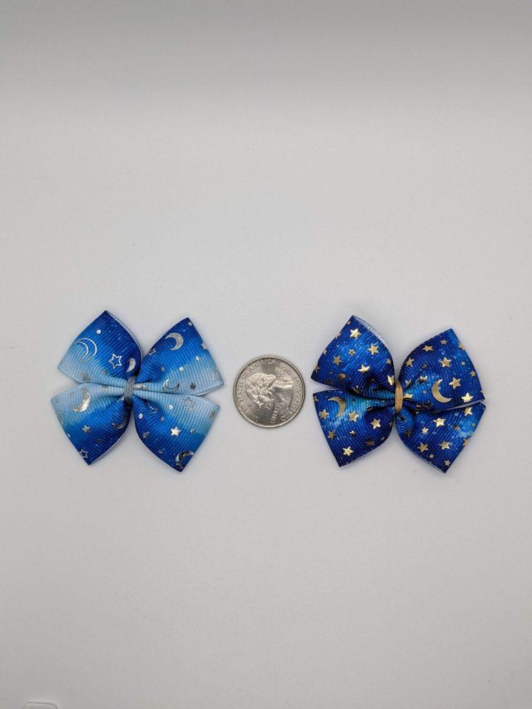 dark blue and gradient blue ribbon bows next to quarter