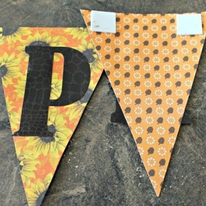 Attaching scrapbook paper to burlap in a fall pumpkin banner craft project for fall.