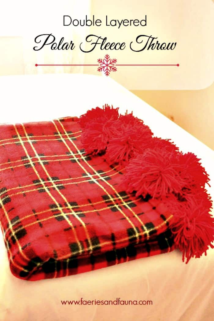 A thick warm fleece blanket diy project. This Christmas throw blanket is a DIY fleece throw with hand made pom poms.