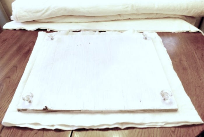 The underside of a DIY ironing table that shows the plywood and quilt padding.