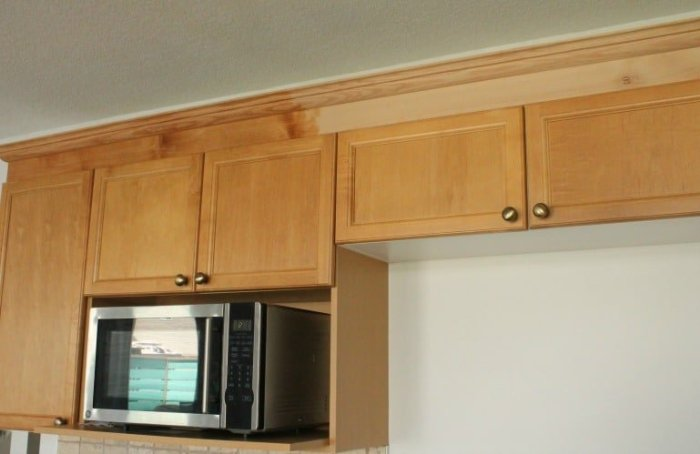 Before and after of natural stain on DIY oak moulding for kitchen cabinets.