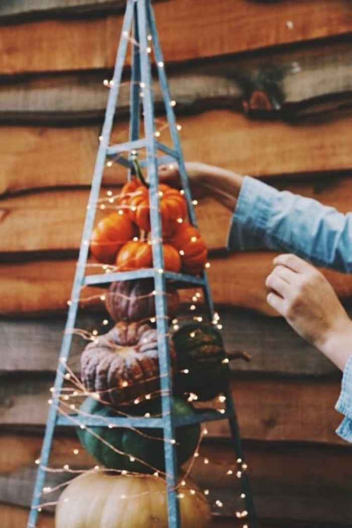 Fall outdoor decor using lights. Layers of pumpkins surrounded with miniature lights.