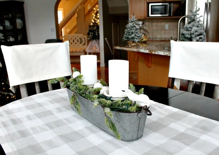 A simple Centerpiece for Christmas using galvanized metal, greenery and white candles. A pretty DIY centerpiece for the Christmas table.