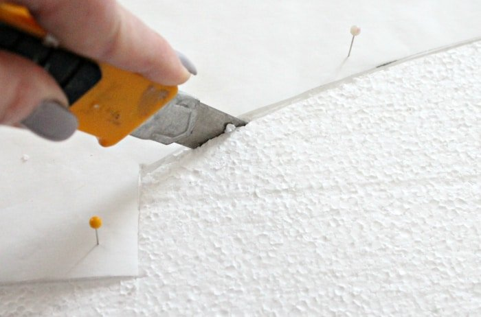 Cutting the edge of a cornice box valance project with a utility knife.