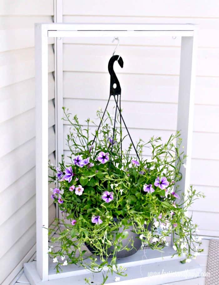 Ugly plastic hanger on a pretty wood plant hanger. Adding screws into the box of a DIY Hanging planter. DIY Planters, DIY Pot hangers, DIY Hanging Pots, DIY Hanging flower pot, DIY outdoor hanging planter.