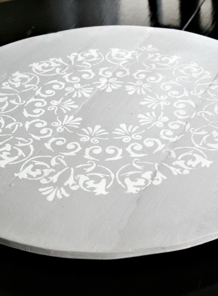 A stenciled mandala on a DIY lazy susan made from pallet wood