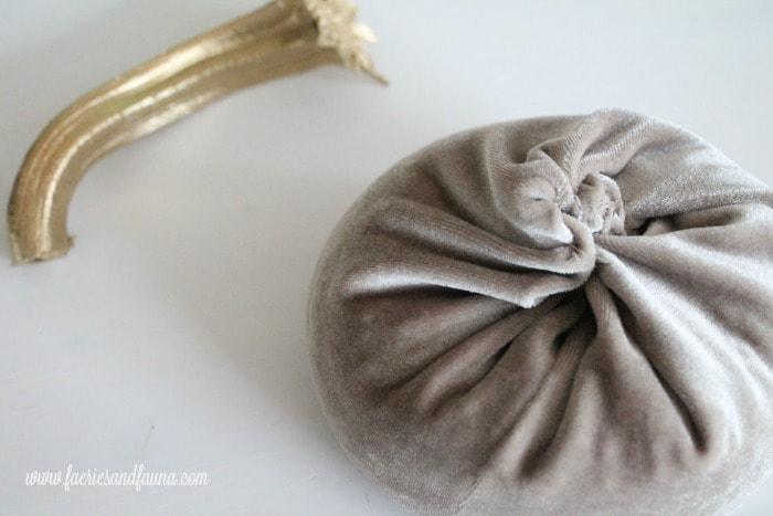 Twisting the top of a DIY velvet pumpkin fall craft.