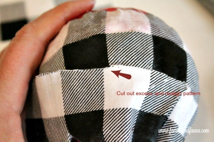 Removing excess buffalo check fabric on a DIY Christmas ornament to realign the pattern.