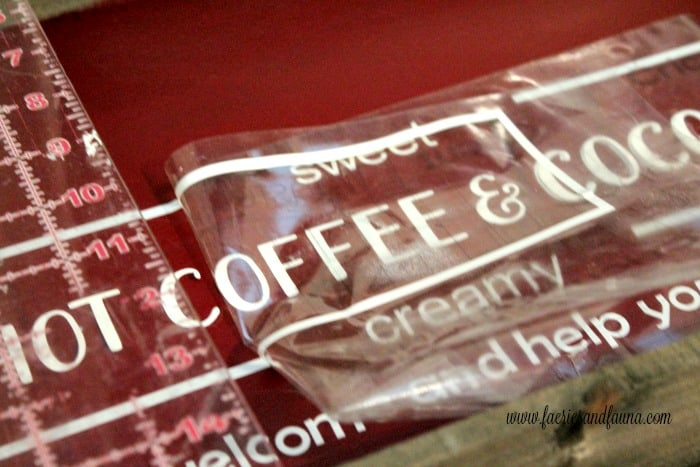 Removing transfer tape from vinyl on a DIY hot chocolate bar sign.