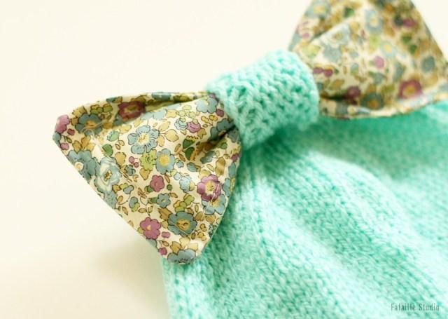 Un gros noeud molletonné sur un bonnet tricoté