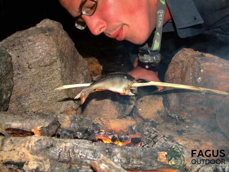 Mathias Michielsen, oprichter van Fagus Outdoor, blaast in vuur met vis erboven