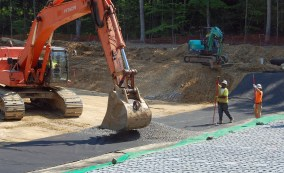 Crushed stone being laid over black geotextile fabric