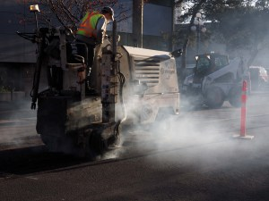 Worker driving yellow grinding machine to mill pavement on street