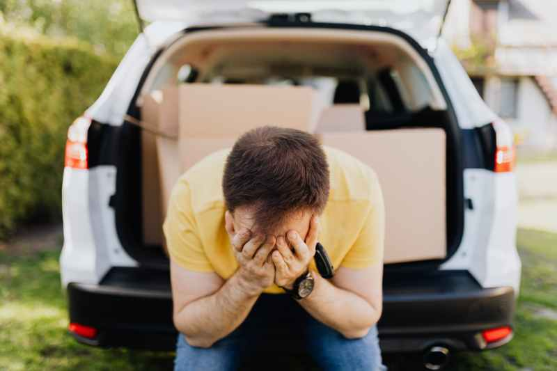man covering face with hands near car trunk
