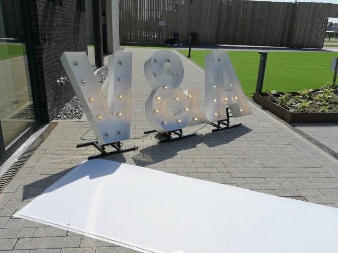 loper en verlichtte letters als decoratie in een huwelijk