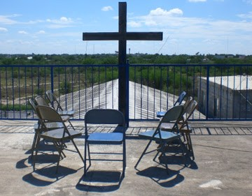 In front of the cross on the roof of the Miguel Aleman church