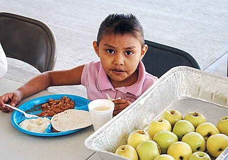 A young girl eating at the nutrition program in Miguel Aleman
