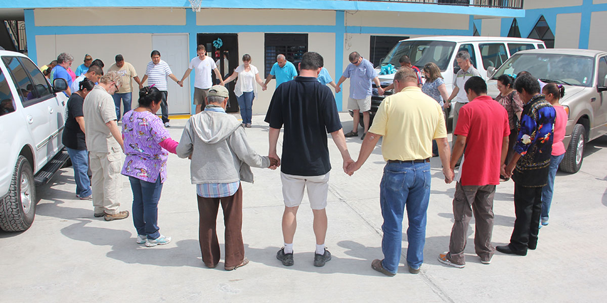The Board of Directors praying with the staff and volunteers in Reynosa