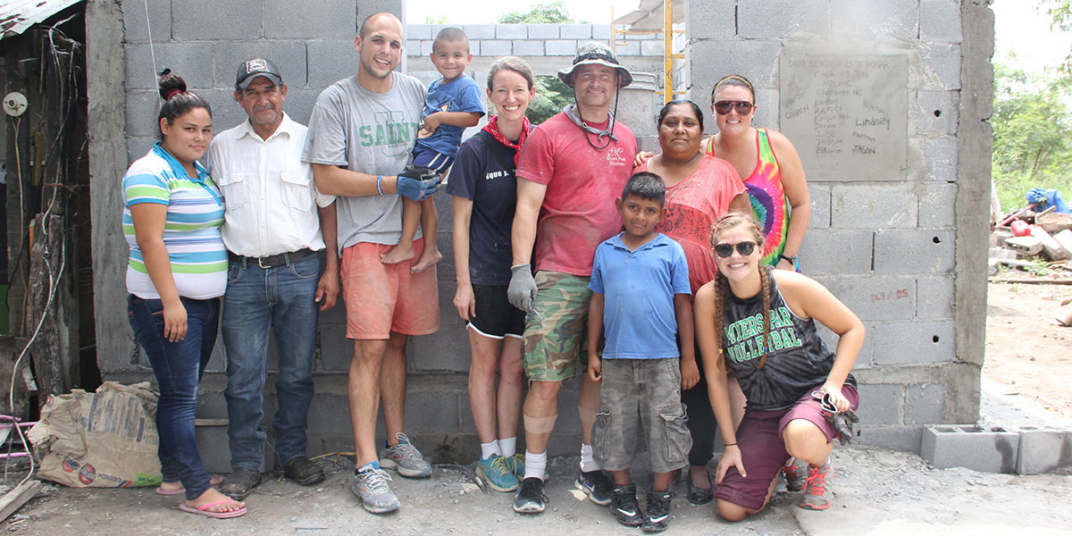 A group and a family in front of a recently completed house in Mexico