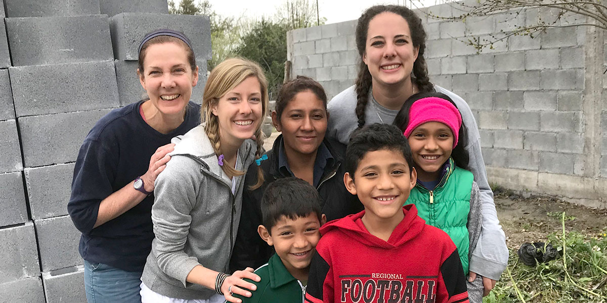 Colleen and her mom and sister with a family they helped build a home for in Reynosa