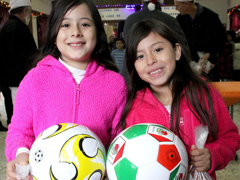 Two girls with their new soccer balls at the Christmas fiesta