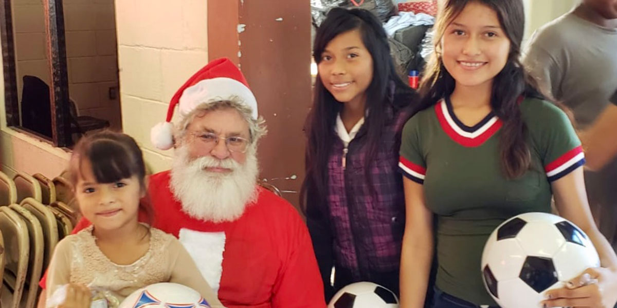 Girls with their new soccer balls and Santa at the Christmas fiesta in Reynosa