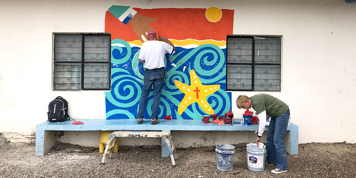 A team from Indiana painting a mural in Naranjito