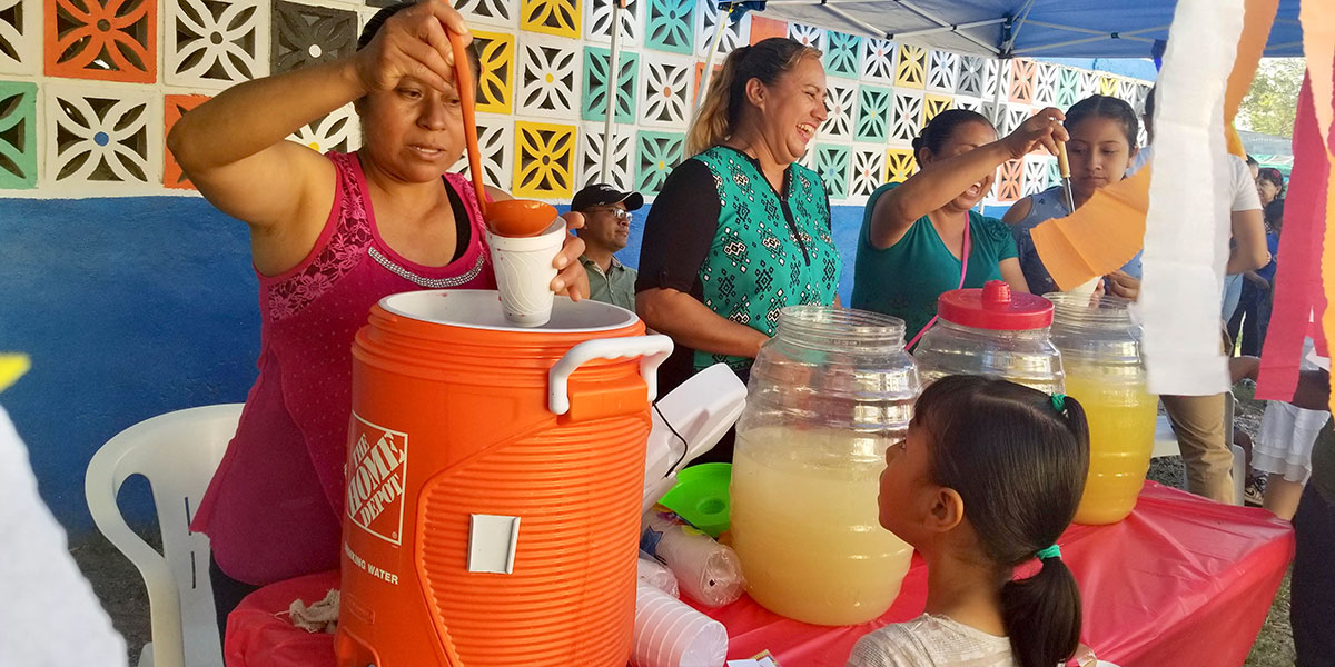 Serving drinks and food to the kids at the Childrens Day fiesta in Naranjito