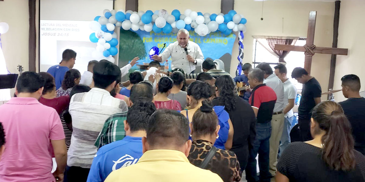 David and the church congregations praying over Pastor Carlos on Dia del Pastor