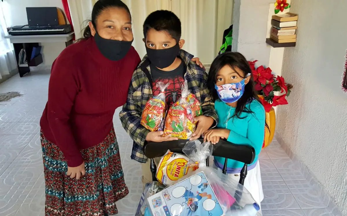 A family receiving a grocery package in Miguel Aleman Mexico
