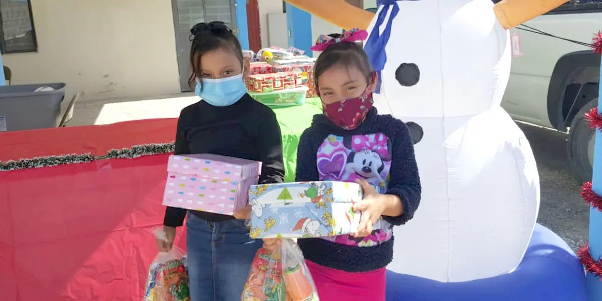Kids receiving gift boxes for Christmas in Miguel Aleman Mexico