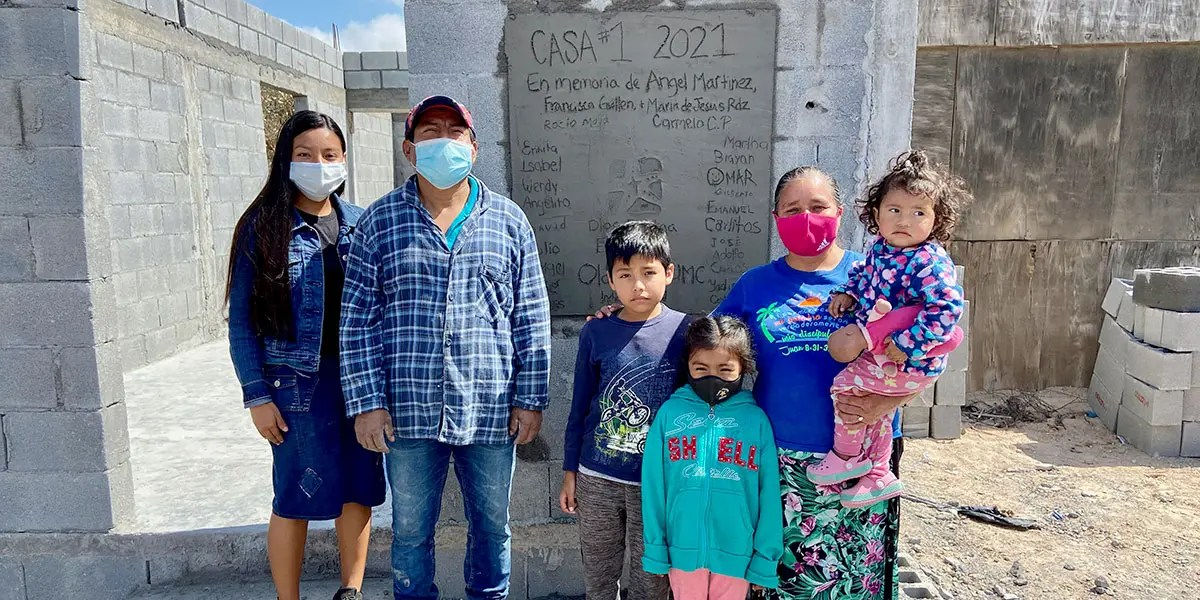 The family of Casa 1 in front of their new home