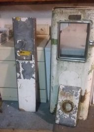Photo of removed doors, side panels, and top of salvaged vintage Bowser gas pump.
