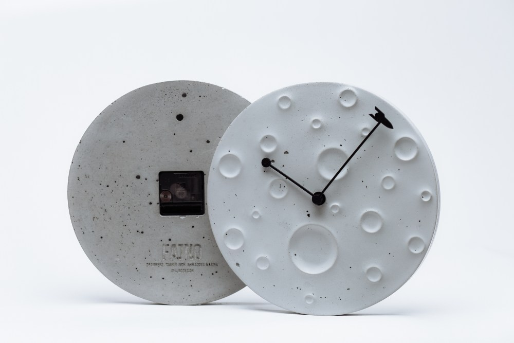 Wall clock made of concrete in the form of the moon ?Around the Moon in 60 Minutes?