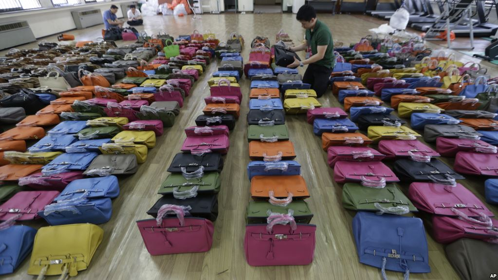 A police official checks some 400 counterfeit bags at Jungbu police station in Seoul, South Korea, Wednesday, June 1, 2016. The fakes of high-end brands such as Hermes were seized during the arrests of four people who allegedly manufactured and sold the goods in South Korea, according to Yonhap news agency. All the counterfeit items will be disposed of by incineration. (AP Photo/Ahn Young-joon)