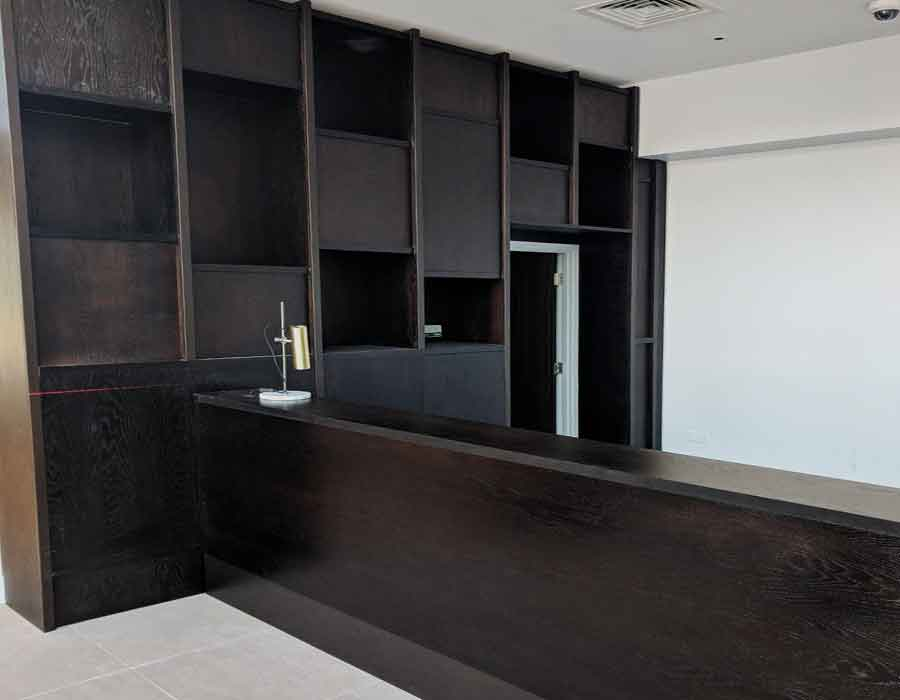 bespoke-dark-wood-reception-desk,-storage-and-display-unit