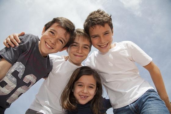 Grupo de niños cogidos por los hombros sonriendo