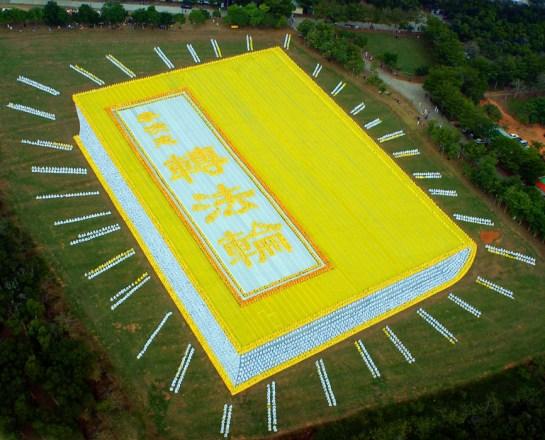 2009年11月21日,來自海外九個國家與台灣當地共六千名法輪功學員,將指導修煉的《轉法輪》排成金光燦爛的立體書。(明慧網)