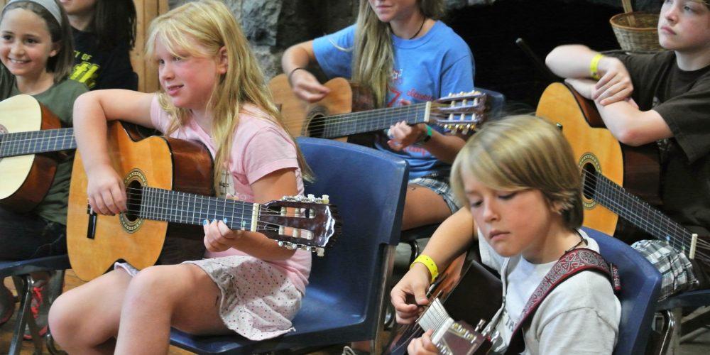 FAME Campers strum on guitars