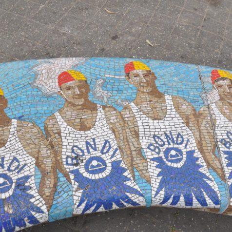 (C) Jule Reiselust: Schwimmermosaik auf Bank auf Promenade am Bondi Beach