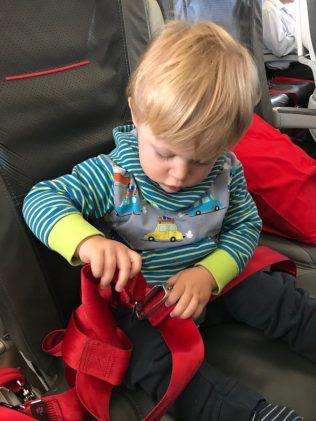 (C) Jule Reiselust: Noah probiert schon mal das Anschnallen. Für Start und Landung muss er allerdings noch auf unseren Schoss.