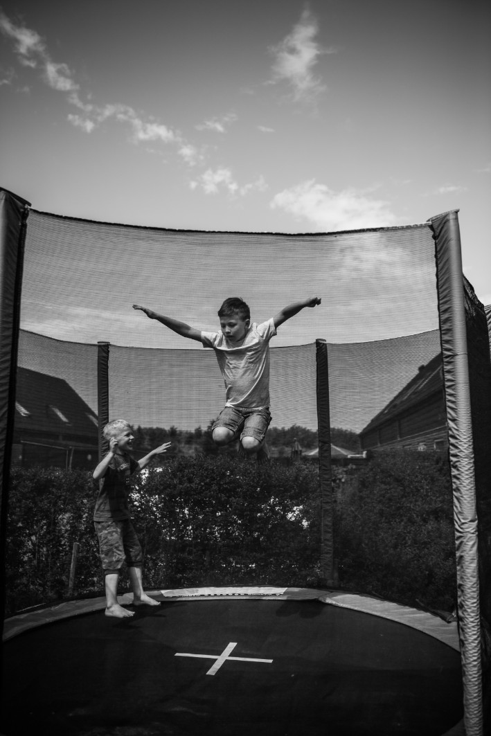 Siblings doing tricks on a trampoline
